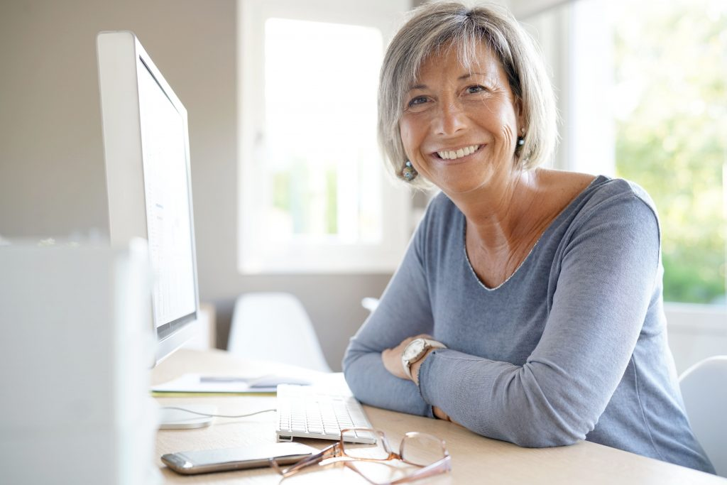 mature business woman smiling and confident at computer