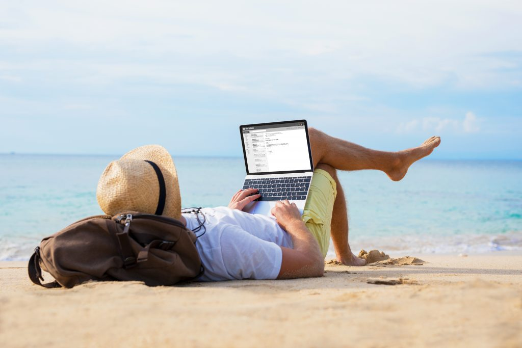 man working on laptop on a beach