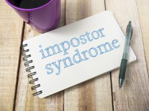 notebook with words imposter syndrome