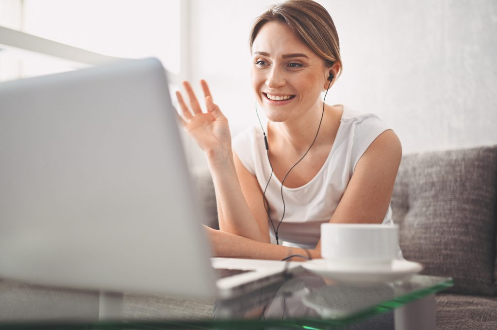 happy female businesswoman sitting at a computer with a mug of coffee