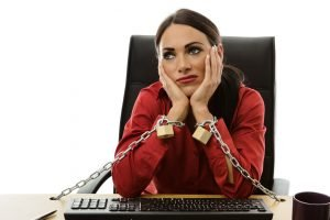 unhappy worker stuck at her job chained to her desk