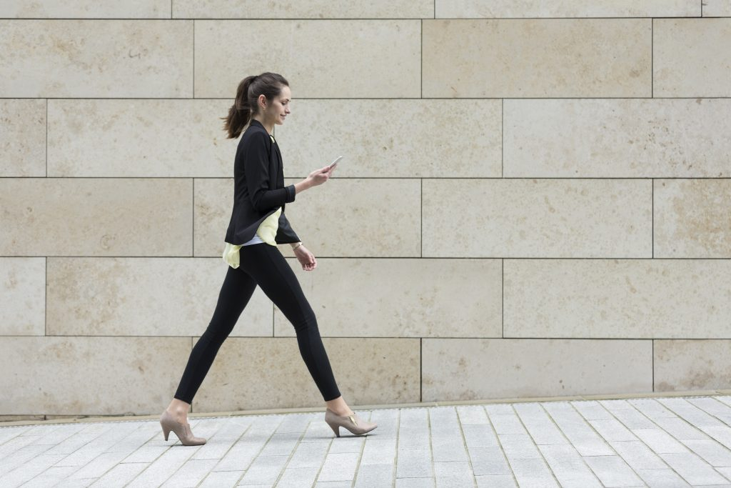 young business woman taking a walk while doing work on her phone
