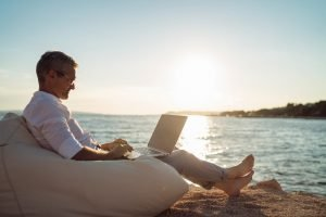 professional freelancer doing a job you can do from anywhere on a beach in a beautiful location